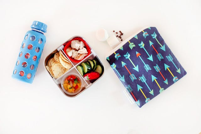 Five lunchbox lunchable hacks that are easy to put together, packed full of nutrients to fuel their school day and can absolutely be made ahead of time so the morning of is still as easy as reaching in the refrigerator. | Healthy Lunchables by popular Florida lifestyle blog, Fresh Mommy Blog: image of a metal bento box filled with tortilla chips, salsa, cucumber, chopped chicken, and peppers.