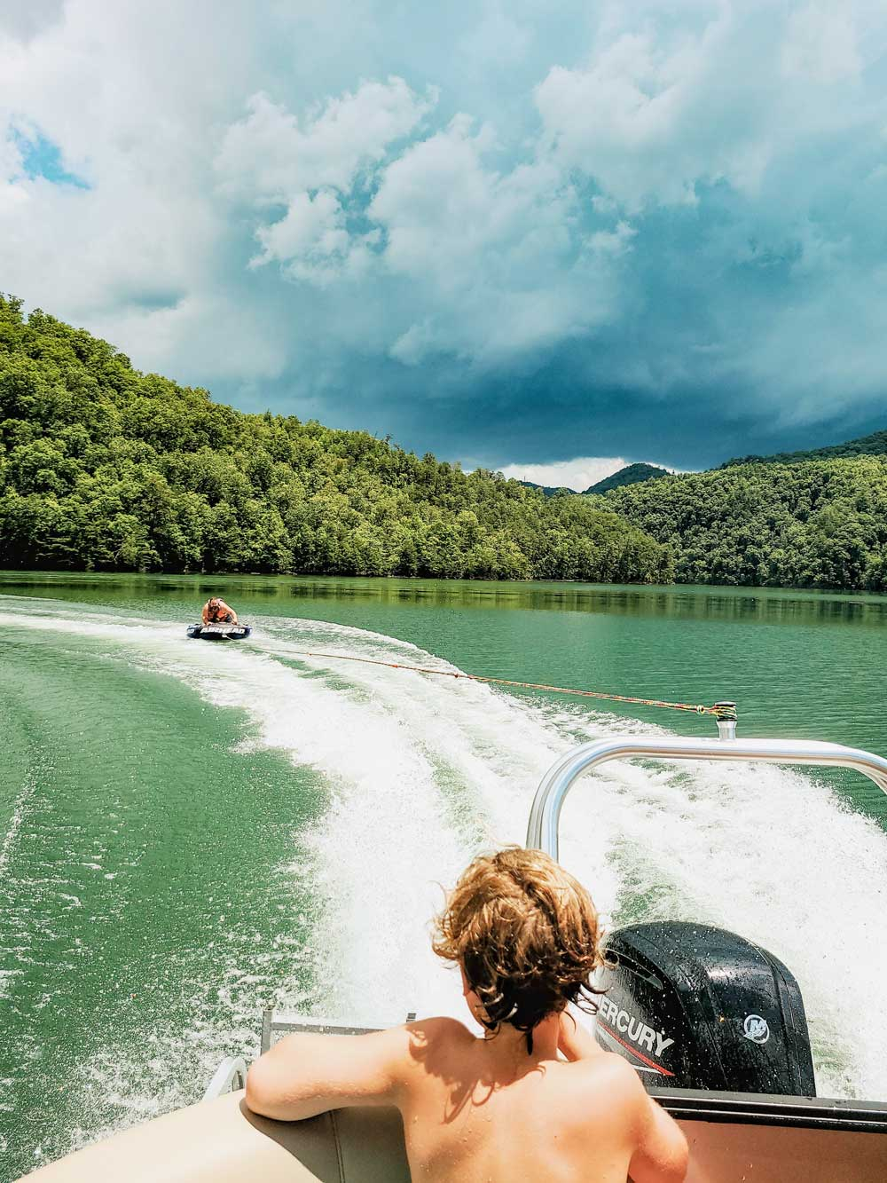 Best Things to Do in Bryson City NC with Kids - Boating on Lake Fontana.   Things to do in Bryson City NC by popular Florida travel blog, Fresh Mommy Blog: image of a family boating on Lake Fontana.