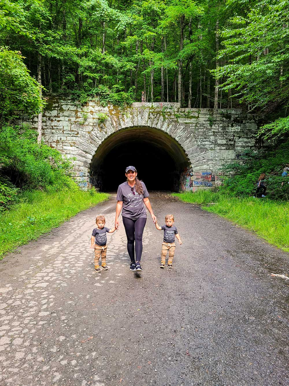 Best Things to Do in Bryson City NC with Kids - The Road to Nowhere   Things to do in Bryson City NC by popular Florida travel blog, Fresh Mommy Blog: image of mom holding her twin boys hands and walking on The Road to Nowhere.