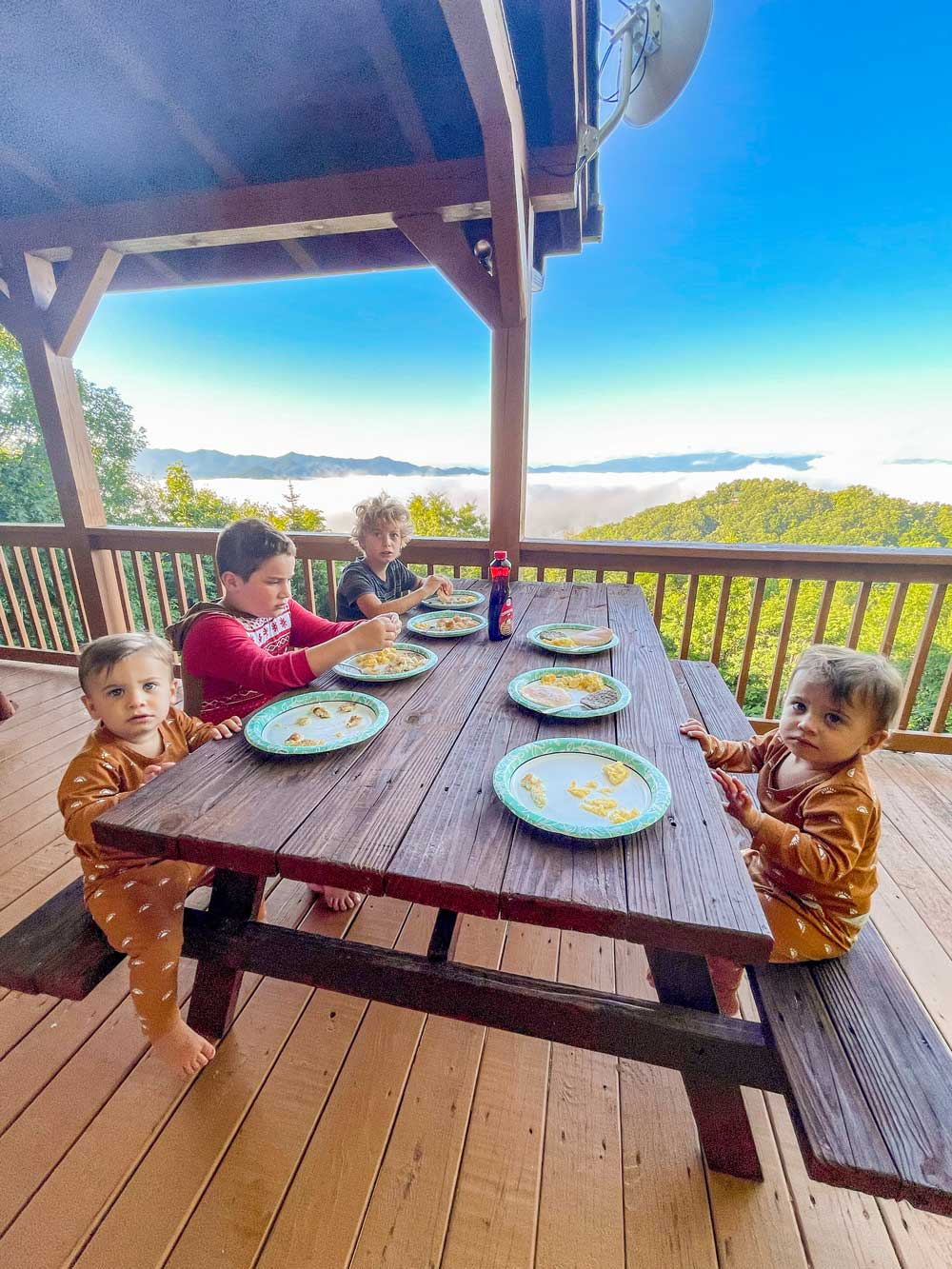 Best Things to Do in Bryson City NC with Kids   Things to do in Bryson City NC by popular Florida travel blog, Fresh Mommy Blog: image of some boys sitting outside on a cabin deck and eating breakfast.