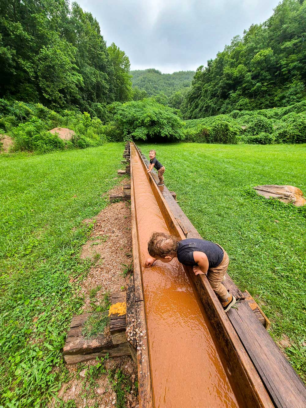 Best Things to Do in Bryson City NC with Kids - Try Gem Mining with the Family   Things to do in Bryson City NC by popular Florida travel blog, Fresh Mommy Blog: image of young twin boys mining for gems.
