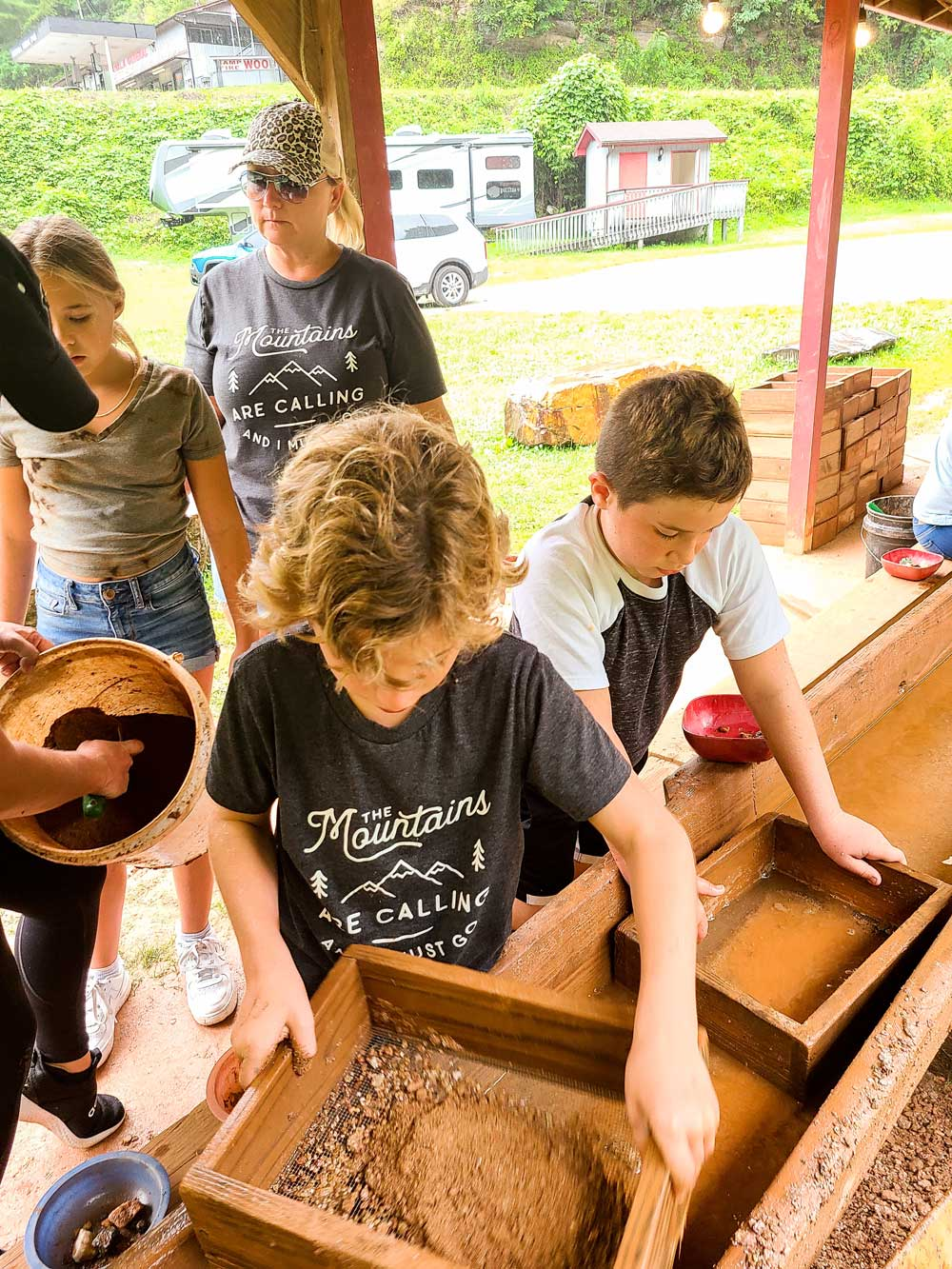 Best Things to Do in Bryson City NC with Kids - Try Gem Mining with the Family   Things to do in Bryson City NC by popular Florida travel blog, Fresh Mommy Blog: image of two young boys mining for gems.