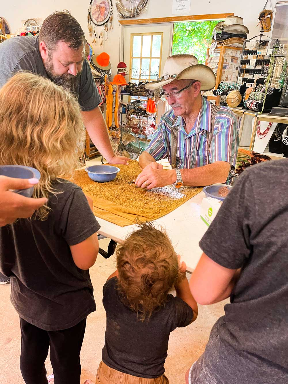 Best Things to Do in Bryson City NC with Kids - Try Gem Mining with the Family   Things to do in Bryson City NC by popular Florida travel blog, Fresh Mommy Blog: image of a dad and his kids looking at gems in a gem shop.