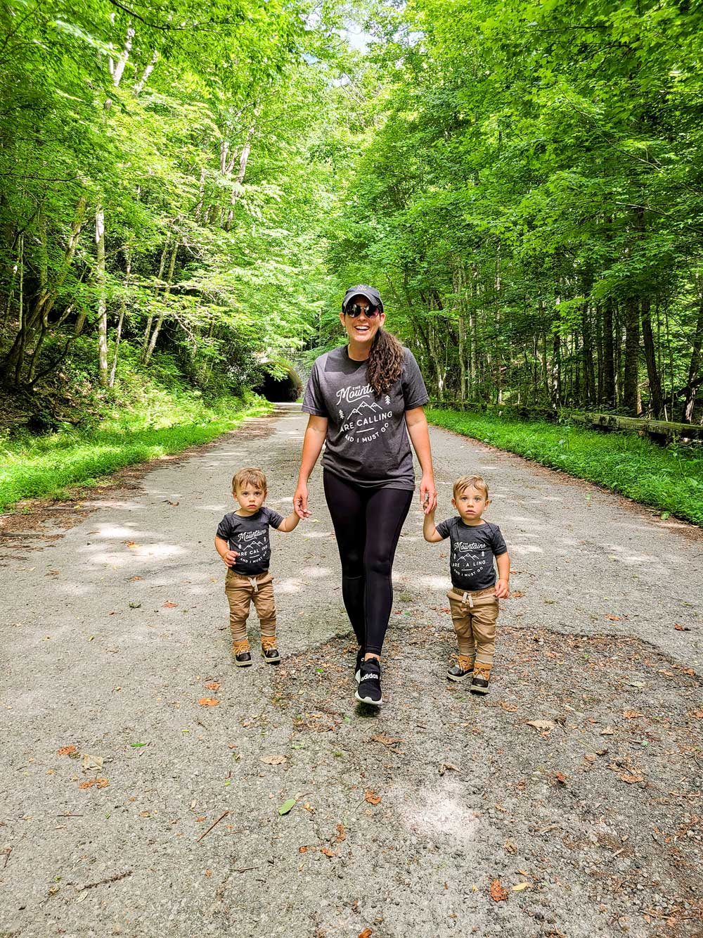 Best Things to Do in Bryson City NC with Kids   Things to do in Bryson City NC by popular Florida travel blog, Fresh Mommy Blog: image of a mom holding her twin boys hands and walking down a paved path in a forest.