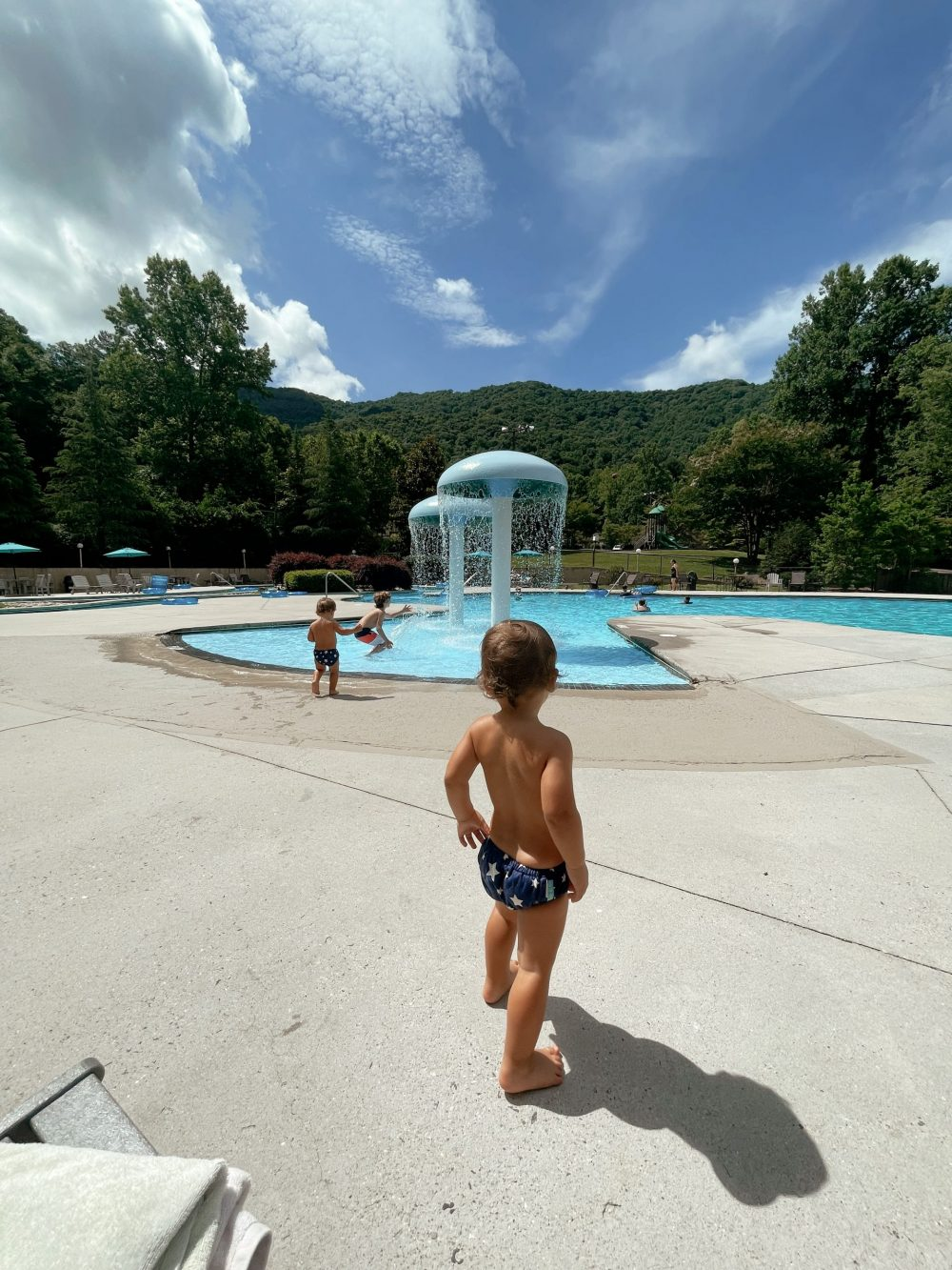 Best Things to Do in Bryson City NC with Kids - Fontana Village Pool   Things to do in Bryson City NC by popular Florida travel blog, Fresh Mommy Blog: image of a family swimming at Fontana Swimming pool.