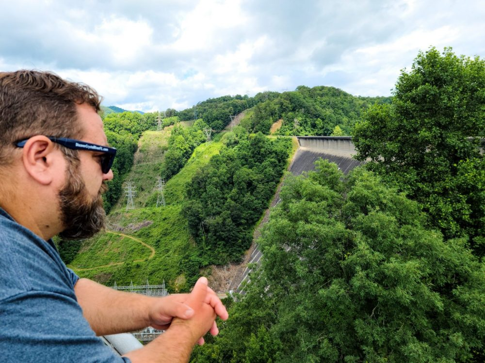 Best Things to Do in Bryson City NC with Kids - Fontana Dam   Things to do in Bryson City NC by popular Florida travel blog, Fresh Mommy Blog: image of man standing on top of Lake Fontana Dam.
