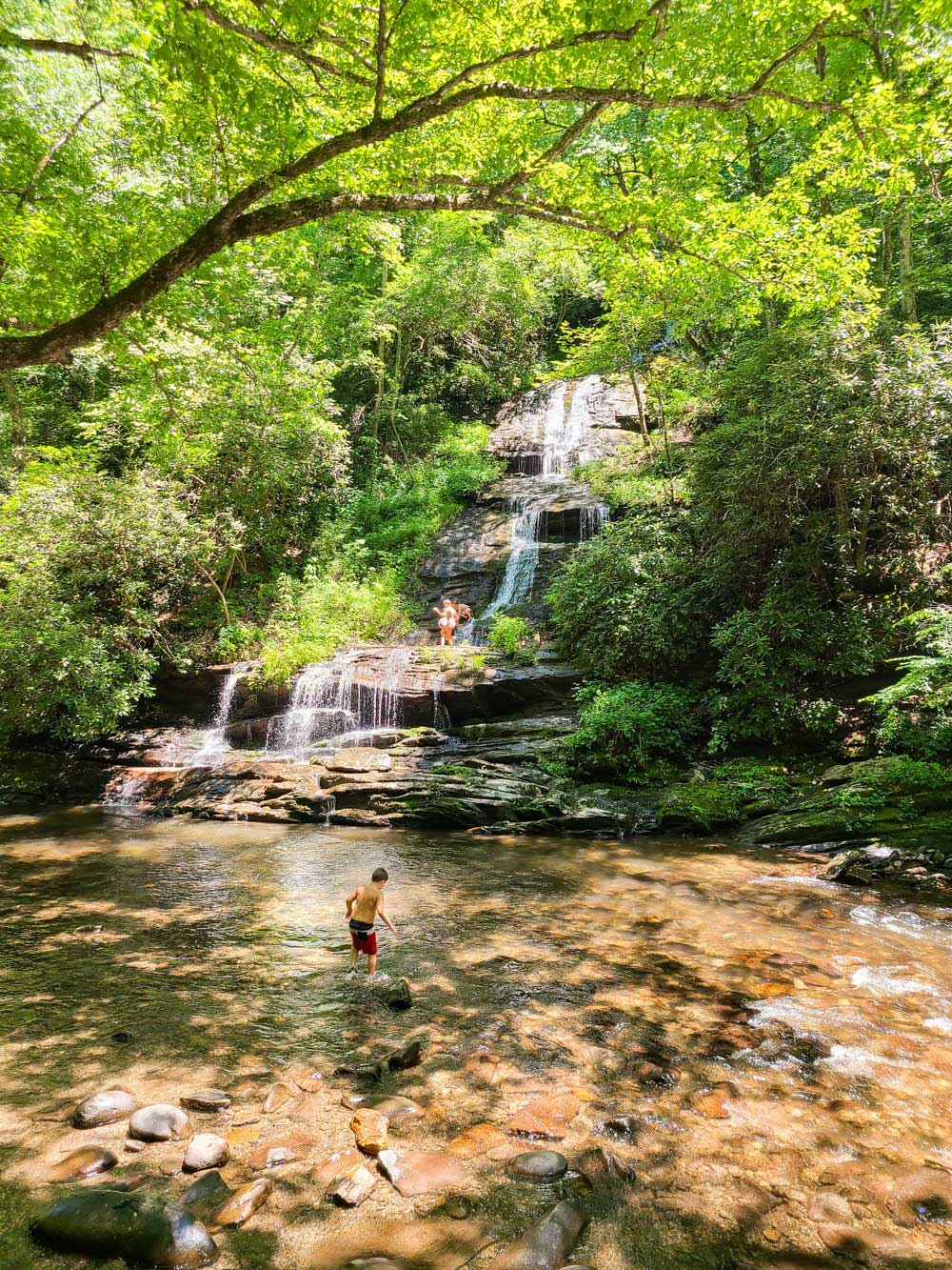 Best Things to Do in Bryson City NC with Kids - Deep Creek River and Tubing   Things to do in Bryson City NC by popular Florida travel blog, Fresh Mommy Blog: image of a family at some Deep Creek River waterfalls.