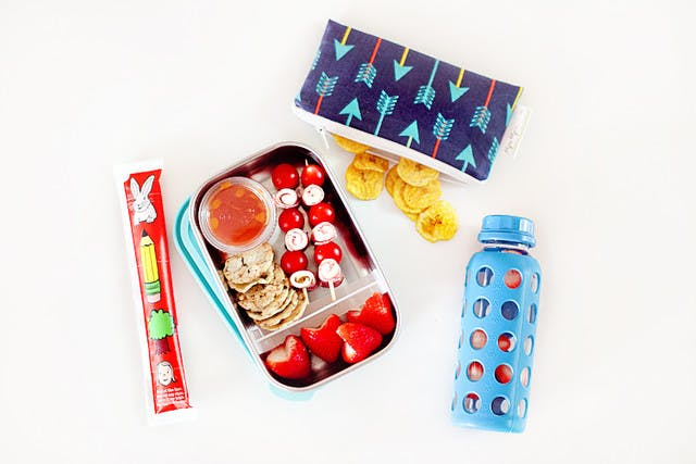 Five lunchbox lunchable hacks that are easy to put together, packed full of nutrients to fuel their school day and can absolutely be made ahead of time so the morning of is still as easy as reaching in the refrigerator. | Healthy Lunchables by popular Florida lifestyle blog, Fresh Mommy Blog: image of a metal bento box filled with tomato and deli meat kabobs, crackers, pizza sauce, and strawberries, next to a go-gurt and water bottle.