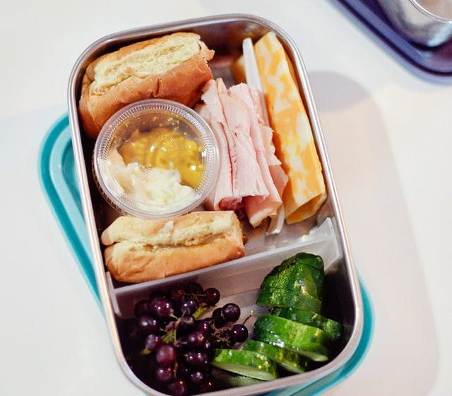 Five lunchbox lunchable hacks that are easy to put together, packed full of nutrients to fuel their school day and can absolutely be made ahead of time so the morning of is still as easy as reaching in the refrigerator. | Healthy Lunchables by popular Florida lifestyle blog, Fresh Mommy Blog: image of a metal bento box filled with deli meat, buns, cheese slices, cucumbers, grapes, and mayo and mustard in a condiments cup.